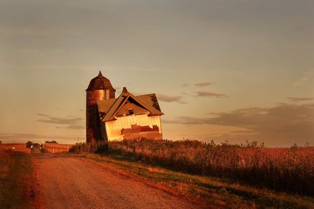 a dilapidated farm house leans as if it was about to fall over. The picture was taken at sunset so the image has a golden glow. photo