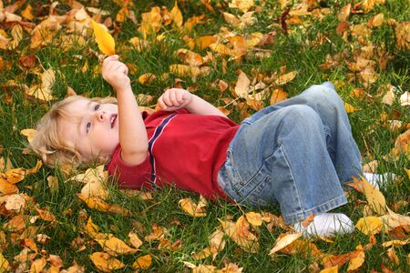 A young boy holds a fall leaf while laying in the leaves