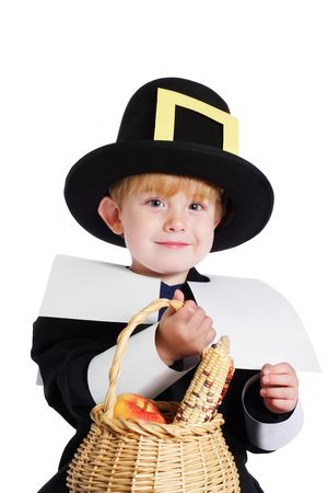 A preschool age boy wearing a pilgrim costume holding a basket of corn and apples (symbolic of the first thanksgiving in america)