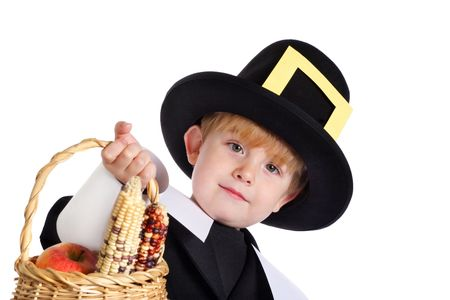 A young boy in a pilgrim costume holds out a basket with indian corn and apples Stock Photo