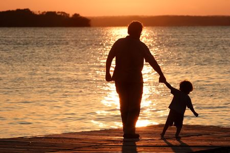 An adult and a child walk out on a dock as the sun sets photo