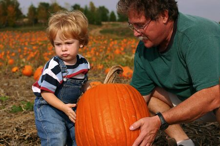 grand sons: Family members work together to lift a pumpkin Stock Photo