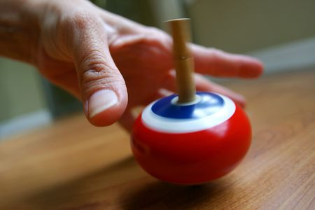 Closeup of a hand, waiting, protecting, reaching for a spinning top photo