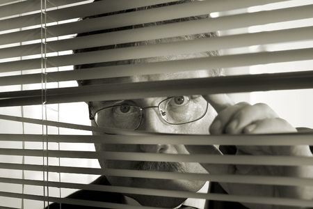 a businessman peers through the blinds
