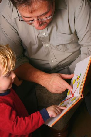 Toddler and adult family member reading a picture book together