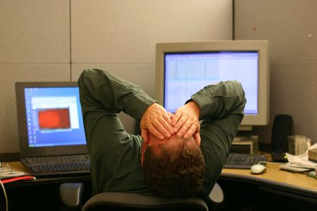Businessman sitting in front of computers covering his face with his hands