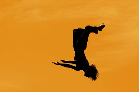 BACKFLIP: Silhouette of a boy doing a backflip in the air