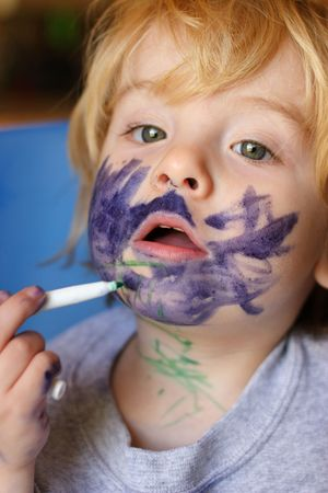Toddler boy exploring art by drawing on his face with a marker