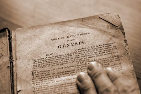 holy god: A hand on the bible with page turned to Genesis