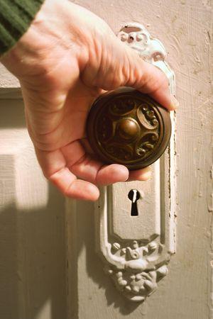 reaches: a hand reaches out to open an antique door
