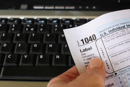 Una persona titular de un impuesto sobre la renta en forma delante de un teclado de computadora