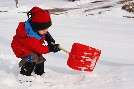a young boy shovels snow with a toy shovel