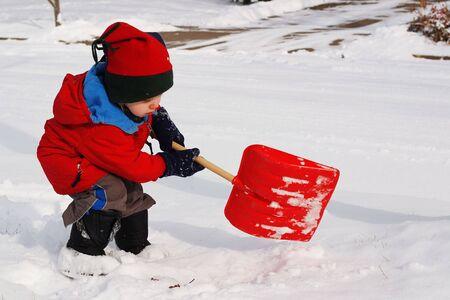 deep freeze: un joven palas de nieve con una pala de juguete  Foto de archivo