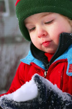 A young boy looks  at snow in his glove after the first snowfall of the season