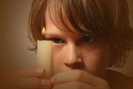 fixate: Boy staring intently at a burning candle he is holding