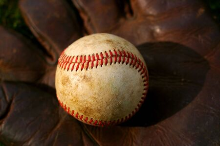 Closeup of an old baseball on a vintage glove Stock Photo
