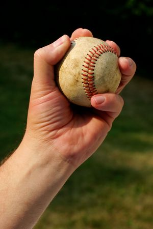 grasp: A persons hand gripping an old  baseball