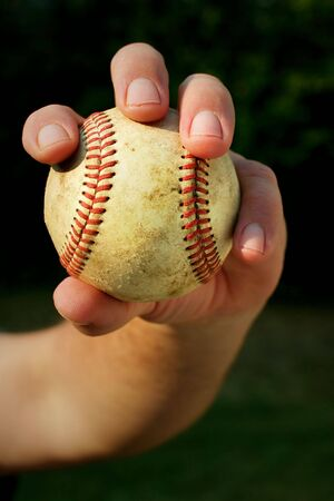 A persons hand gripping an old  baseball