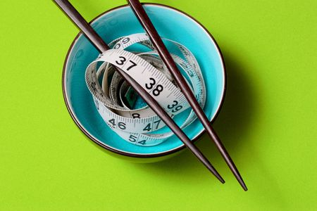 A light blue bowl on Green Background with a tape measure and chopsticks Reklamní fotografie