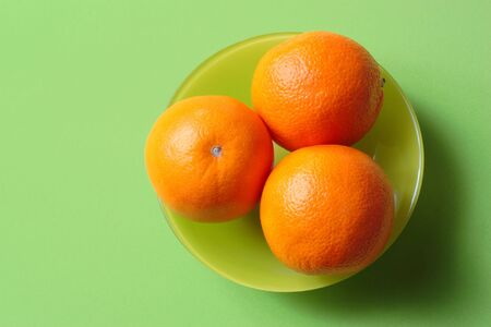 A green bowl with three oranges on a green background Stock Photo - 2818080