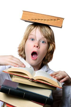 A surprised boy holds a book open while balancing another book on his head Stock Photo - 2818101