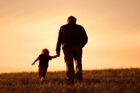 toddler walking: A father and son walking and holding hands