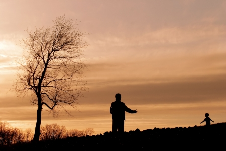 Silueta de un padre apertura de sus brazos a un ni�o corriendo hacia �l