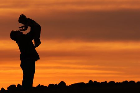 Silhouette of a Man and a Child against a sunset sky