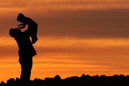Silueta de un hombre y un ni�o contra una puesta de sol cielo  Foto de archivo