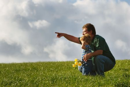 A father with his arm around his son, points toward the break in the clouds where the sun is shining through