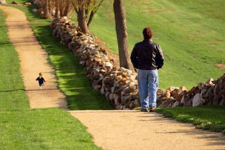 Een volwassen horloges als kind loopt vooruit op een pad Stockfoto