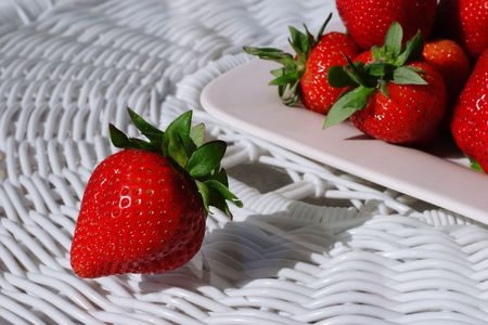 Fresh Ripe Strawberries on a wicker table, lit by the afternoon sun Stock Photo - 2856255