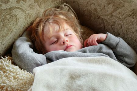 peacefully: A young boy peacefully sleeps on the couch