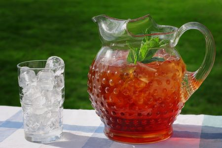 An antique Hobnail Pitcher full of Iced Tea with a sprig of mint. A glass full of ice sits along side, in the afternoon sun photo