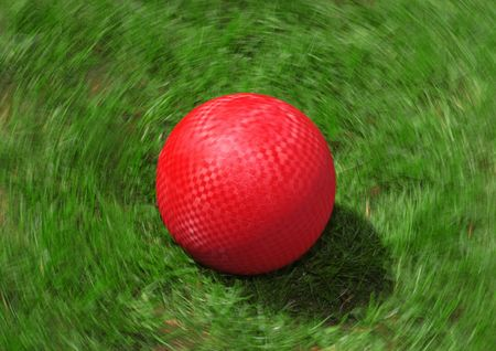 A red ball spins on the grass