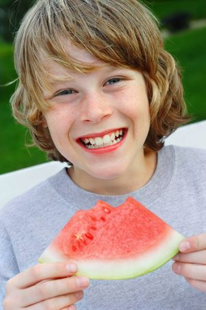 Smiling preteen boy holding a piece of watermelon 版權商用圖片