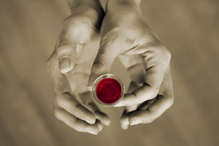 religious service: Hands holding a communion cup, the wine is red and the rest of the image is subdued color