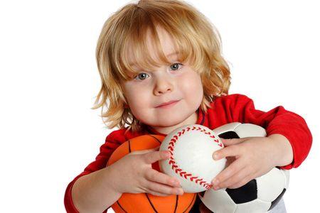 kindergarten toys: Closeup of a young boy holding a basketball, baseball, and soccerball