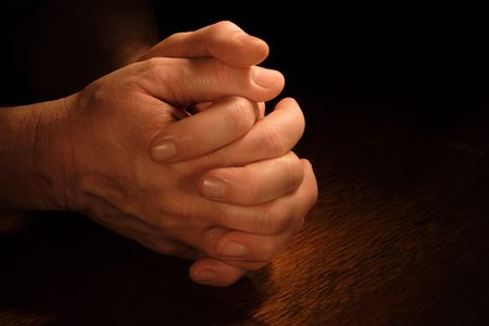 plead: A mans hands folded in prayer with very dramatic lighting