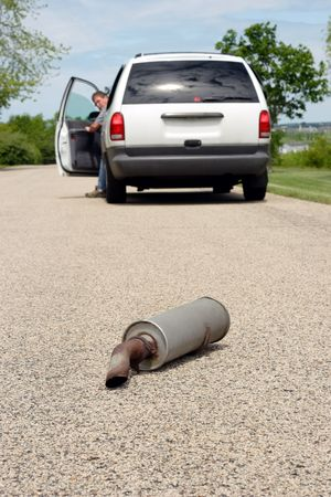 A man is getting out of his car and looks back to see his cars muffler laying on the ground