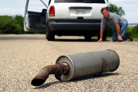 A man kneals on the ground by his car and looks back to see his cars muffler laying on the ground