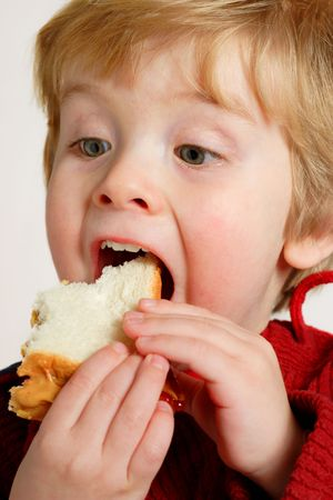 Closeup of a boy eating a peanut butter and jelly sandwich