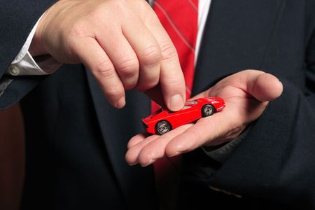 A business man holds a model car in his hand