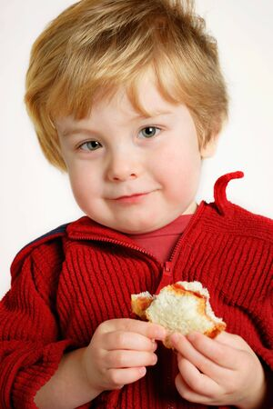 A young boy holding a peanut butter and jelly sandwich (focus is on the face) Stock Photo - 2853140