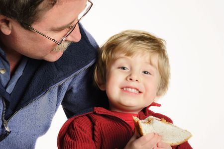 Father smiling at son who is holding a peanut butter and jelly sandwich Stock Photo - 2853112