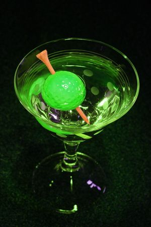 black hole: A golf ball olive with a tee toothpick in a martini against a black background (symbolic of the 19th hole in golf)