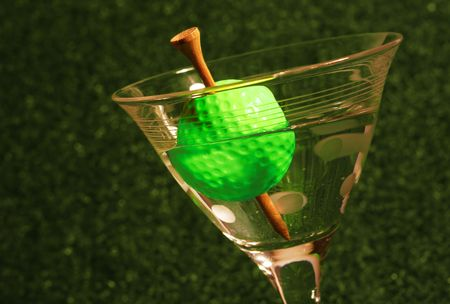 A golf ball olive with a tee toothpick in a martini against a black background (symbolic of the 19th hole in golf)