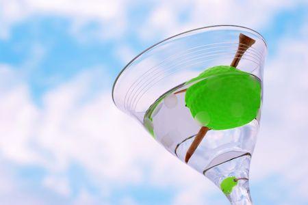 ゴルフボール (ゴルフ 19 ホールの象徴) の雲と青空に対してマティーニで t シャツつまようじでオリーブ