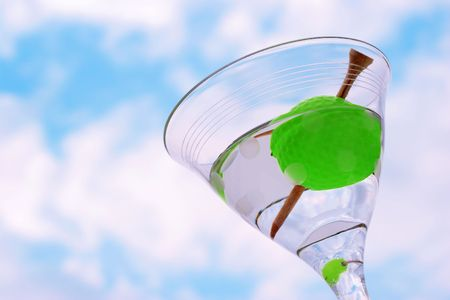 A golf ball olive with a tee toothpick in a martini against a blue sky with clouds (symbolic of the 19th hole in golf)