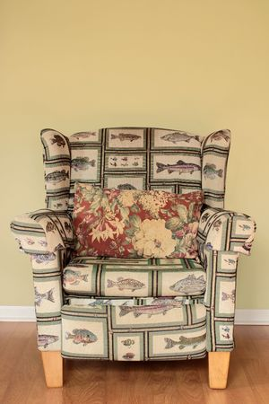 A tacky Arm Chair with a fish pattern well worn and broken in